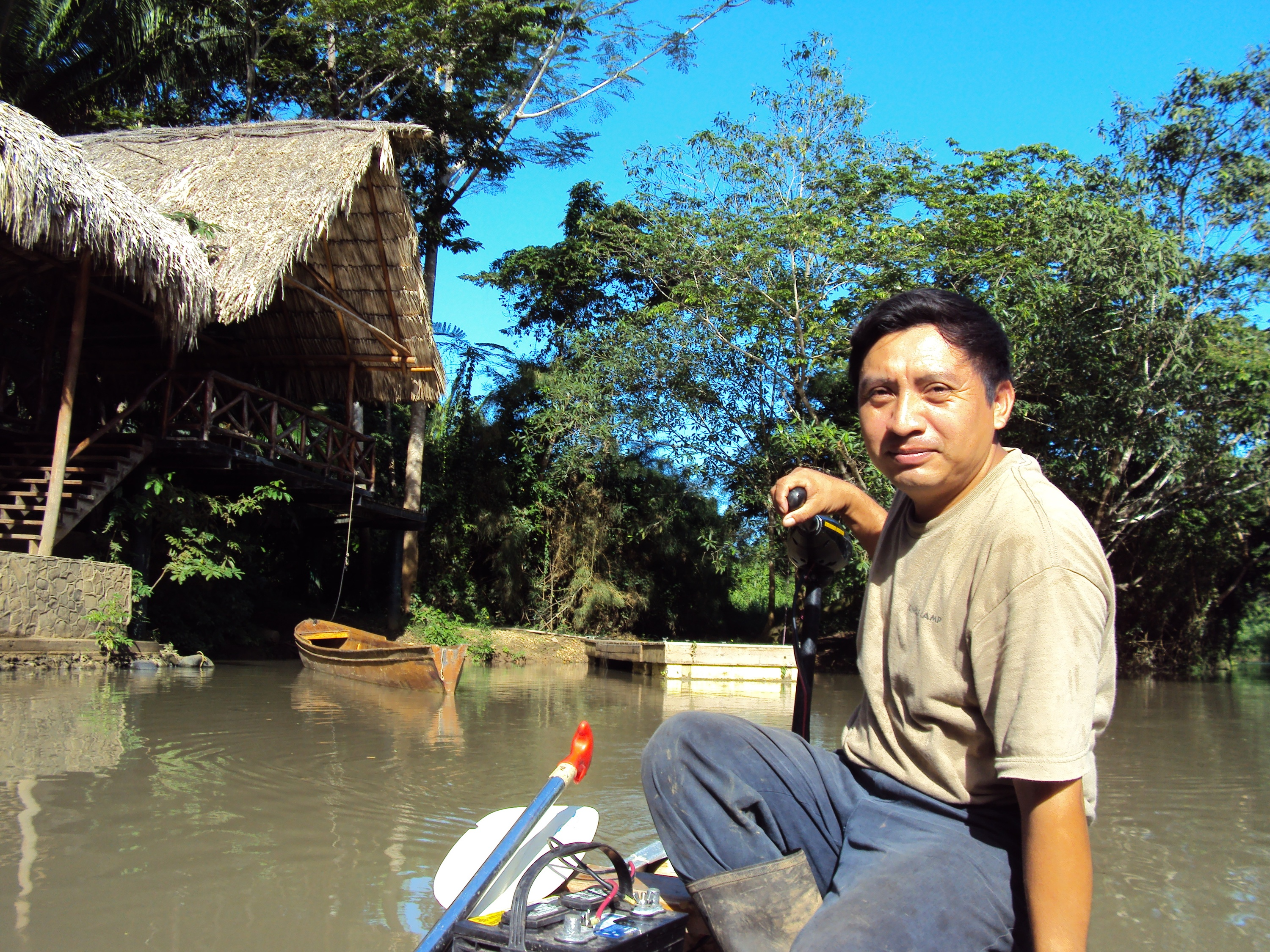 Man in a boat smiles surrounded by water and a thatched hut